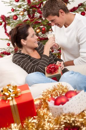 Young couple with glass of champagne in front of Christmas tree photo
