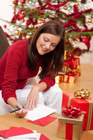 person writing: Attractive brunette writing Christmas cards in front of tree Stock Photo