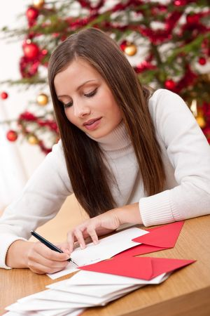 Young woman writing Christmas card in front of tree Zdjęcie Seryjne