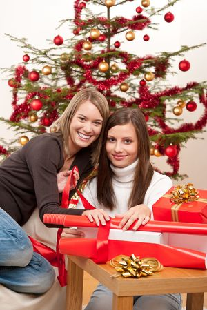 Two women packing Christmas present in front of tree Stock Photo - 5712893