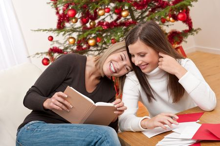 Two young women writing Christmas cards in front of tree Stock Photo - 5712899