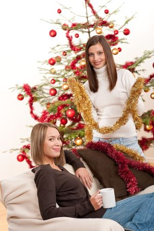 Two cheerful women with Christmas chains and balls in front of tree Stock Photo - 5712871