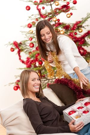 Two cheerful women with Christmas chains and balls in front of tree Stock Photo - 5714168