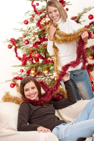 Two young woman having fun with Christmas decoration in front of tree Stock Photo - 5714171