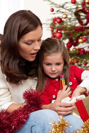 Mother with child opening present on Christmas Stock Photo - 5714607