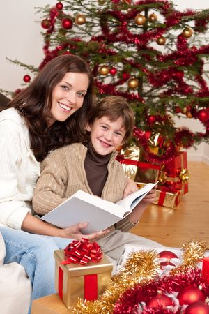 Young mother with son reading book on Christmas in front of tree Stock Photo - 5714609