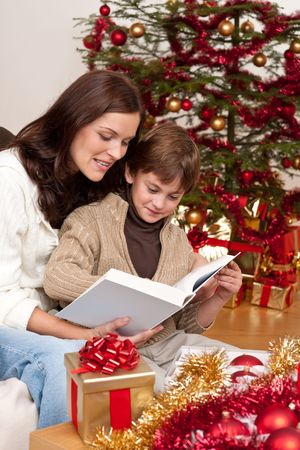 Young mother with son reading book on Christmas in front of tree Stock Photo - 5714613