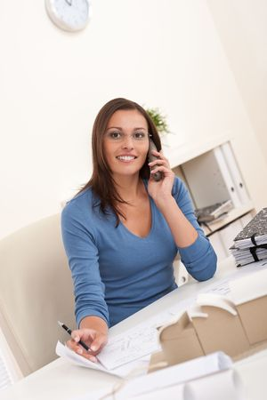 Smiling female architect holding phone and pen sitting at the office photo
