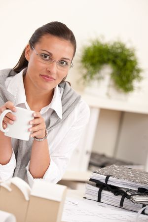 Female architect at the office having coffee break photo