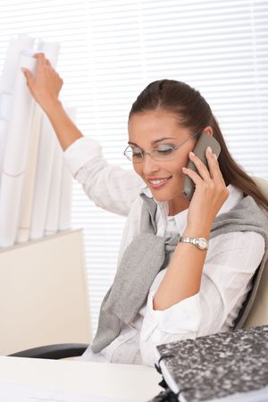 Young businesswoman on the phone sitting at office photo