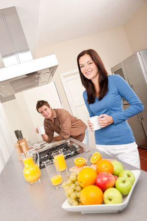Smiling woman and man in the kitchen, having coffee and orange juice photo