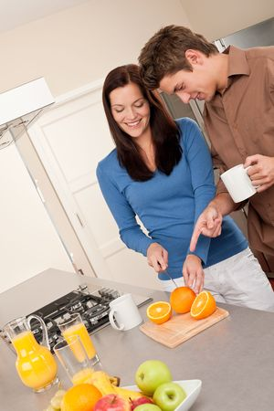 Happy couple preparing food together, cutting oranges Stock Photo - 5786959
