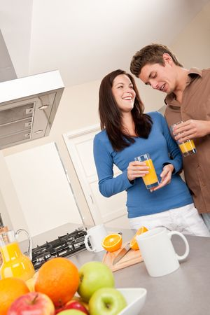 Young man and woman drinking orange juice in the kitchen photo