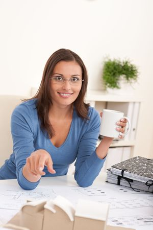 Brown hair female architect sitting at office holding cup of coffee photo
