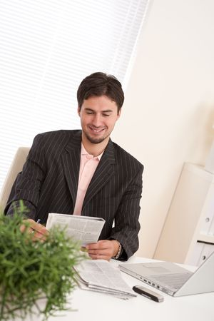 Young modern businessman with laptop and newspaper sitting at the office photo