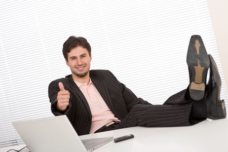 gesturing: Young businessman gesturing at office having legs up