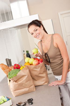 Young smiling woman with groceries holding apple Stock Photo - 5797056