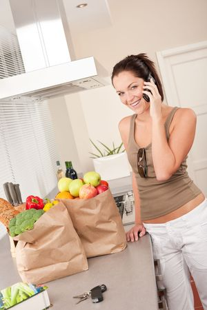 Young smiling woman with groceries on the phone Stock Photo - 5797125