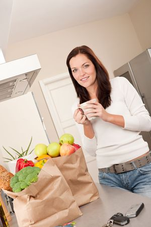 Young smiling woman with groceries drinking cup of coffee Stock Photo - 5797106