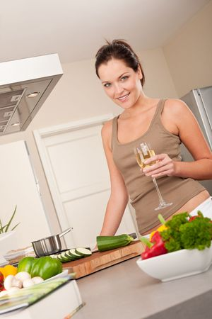 Smiling young woman cooking and holding glass of champagne photo