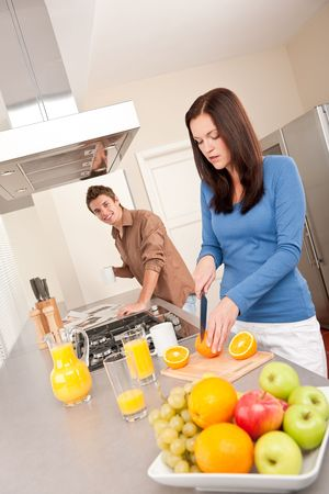 Happy couple preparing food together, cutting oranges photo