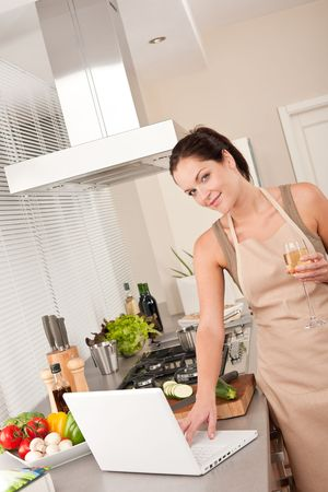Cheerful woman with glass of champagne and laptop in the kitchen cooking photo