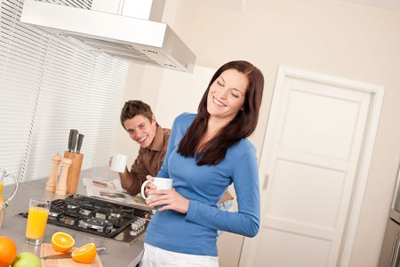 Smiling woman having coffee in the kitchen, man in background photo