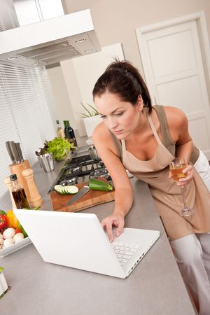 Woman with glass of champagne and laptop in the kitchen cooking photo