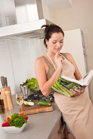 Young brown hair woman reading cookbook in the kitchen photo