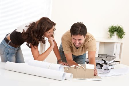 Young man and woman working at architect office with plans photo