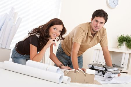 Young man and woman working at architect office with architectural model photo