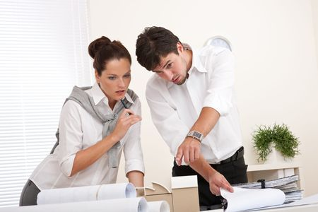 Professional businessman and businesswoman at the office working together photo