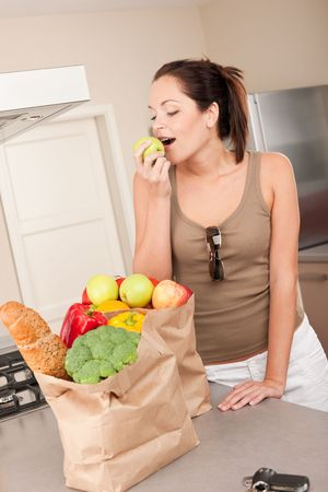 Young smiling woman with groceries in the kitchen biting apple Stock Photo - 5829990