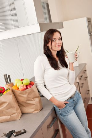 Young smiling woman with groceries drinking cup of coffee in the kitchen Stock Photo - 5830023