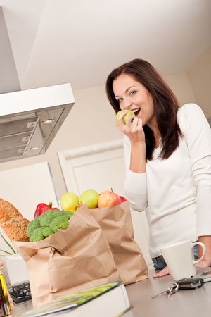 Young smiling woman with groceries in the kitchen biting apple Stock Photo - 5830029