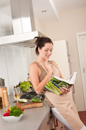 Young woman reading cookbook in the kitchen, looking for recipe Stock Photo - 5830018