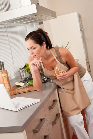 aprons: Woman with glass of white wine and laptop in the kitchen cooking Stock Photo