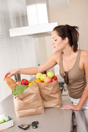 Young woman with groceries in the kitchen with shopping bags photo