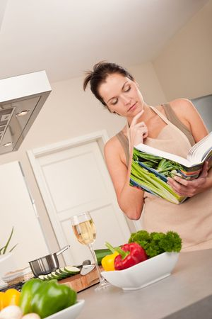 Young woman reading cookbook in the kitchen, looking for recipe photo