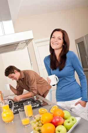 Smiling woman having coffee in the kitchen, man in background Stock Photo - 5854294