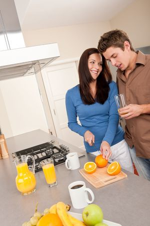 Young woman and man drinking orange juice in the kitchen photo