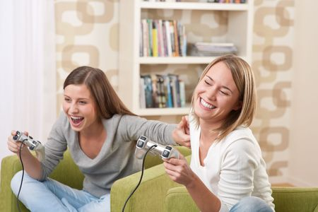 Students - Two female teenager playing video TV game in modern living room photo