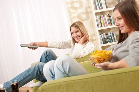 Students - Two female teenager watching television and eating crisps in modern lounge photo