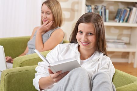 Students - Two female students studying in lounge, reading book photo