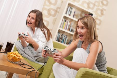 Students - Two happy female teenager playing TV game and having fun photo