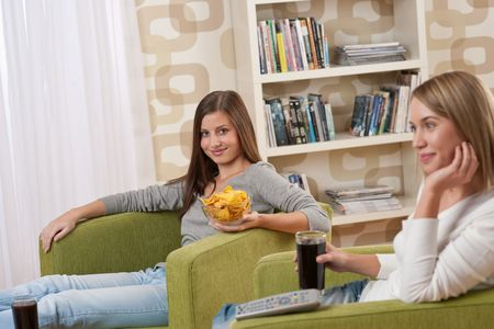 Students - Two smiling female teenager watching television together, eating crisps photo