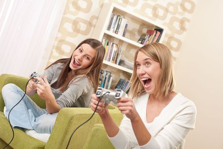 Students - Two female teenager playing video TV game in modern living room Stock Photo - 5931841