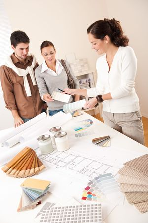 tervező: Female interior designer with two clients at office choosing colors