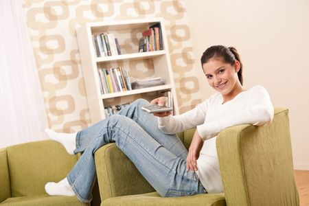 Students - Smiling female teenager watching television in living room holding remote control photo