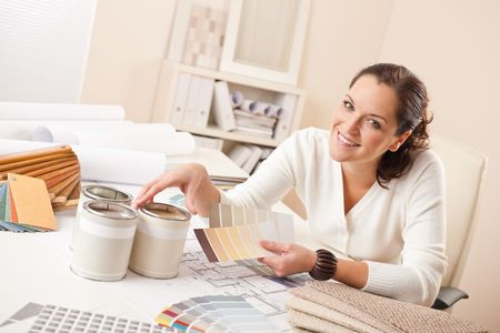 Young female interior designer working at office with color swatch and can of paint photo